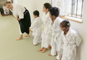 Instructor talking to group of children in aikido class